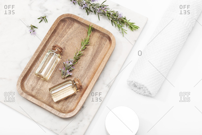 Rosemary essential oil in glass bottle on wooden tray. Salvia Rosmarinus oil