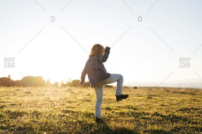 Back view of anonymous adorable active little girl in casual wear playing and dancing in green field while enjoying sunny summer evening in countryside