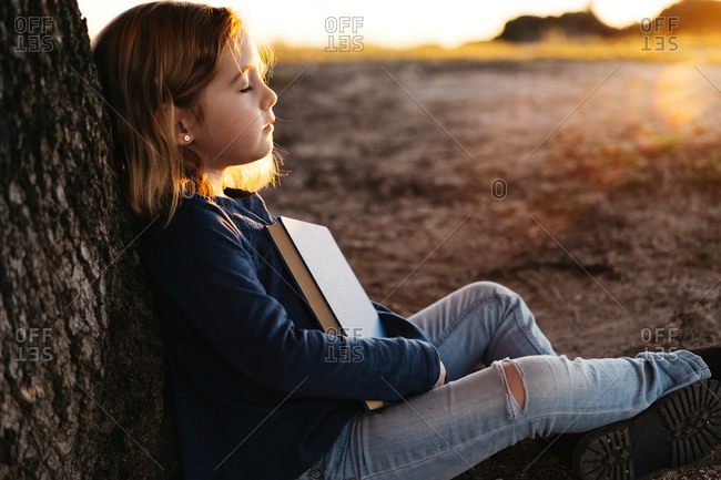 Side view of calm little girl in casual wear with closed eyes holding a fairy tale book while sitting under tree in field in sunny summer evening
