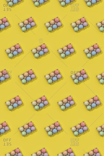 Bright seamless Easter template with white eggs in carton boxes on yellow background