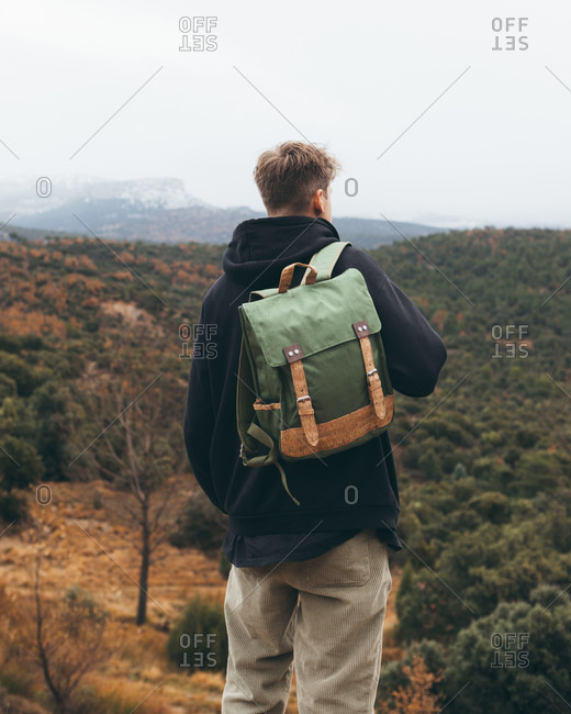 Back view of young male hiker with backpack standing on hill and enjoying beautiful autumn landscape while travelling in mountains