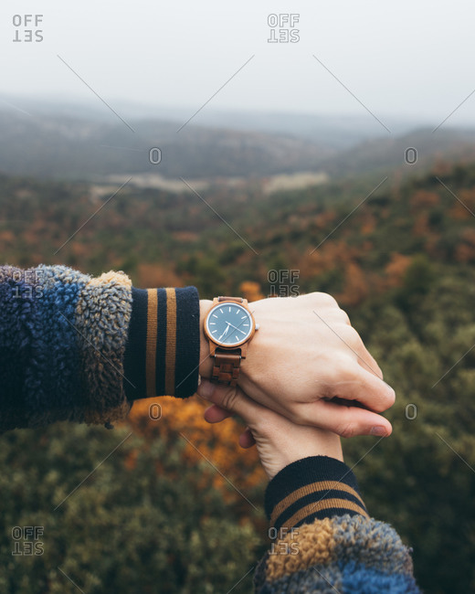 Crop unrecognizable hiker checking time on trendy wristwatch while standing against beautiful autumn scenery with colorful forest and mountains in cloudy day