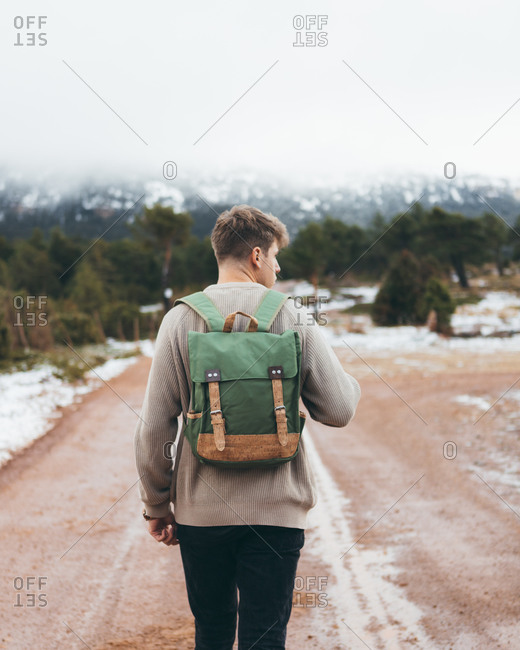Back view of young male traveler in sweater with backpack walking on dirt rural road in cloudy winter day with green forest and snow on roadsides