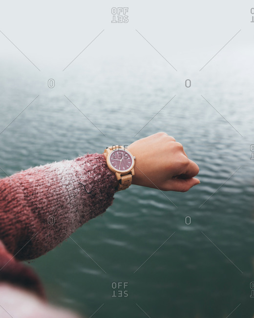 From above crop anonymous female in warm sweater checking time on stylish wristwatch while holding hand over river in cloudy day
