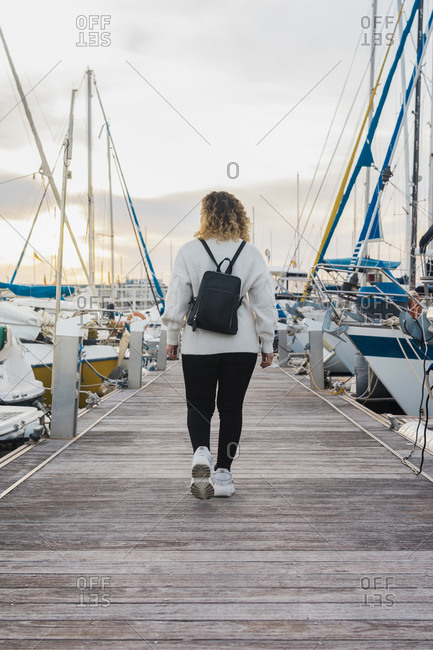 Back view of faceless young lady in casual wear with black backpack walking on wooden pier between modern yachts on sunset