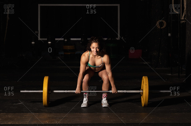 Happy muscular woman win sportswear smiling and lifting heavy barbell over head during intense workout in dark gym