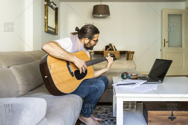 Side view of bearded creative male musician in casual wear sitting on sofa and playing acoustic guitar in modern living room