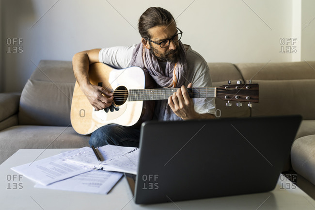 Stylish guitarist on couch in living room