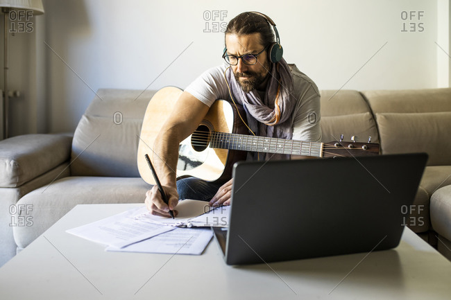 Bearded male musician in eyeglasses sitting on couch with guitar and writing notes on table while using headphones and laptop