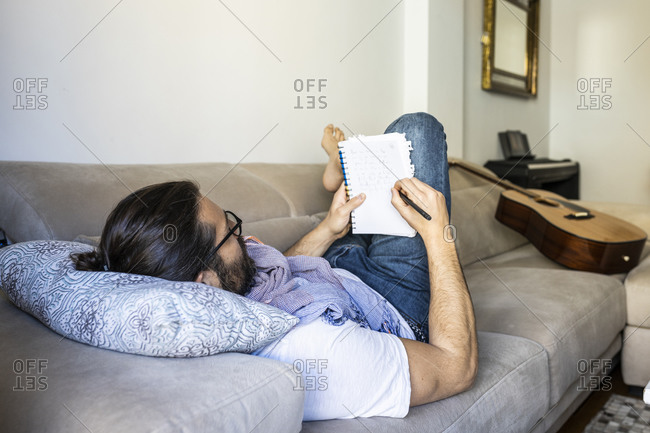 Back view of smart bearded man in casual wear lying on comfortable couch while taking notes in stylish living room