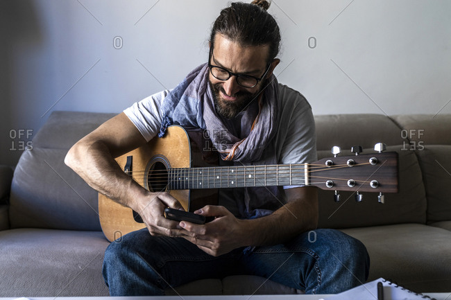 Content bearded male musician sitting on couch with guitar while surfing on mobile phone and smiling in modern living room