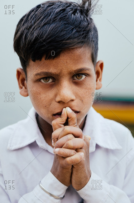Varanasi, India - FEBRUARY, 2018: Serious Indian boy from poor family wearing white shirt touching lips with folded hands and looking at camera
