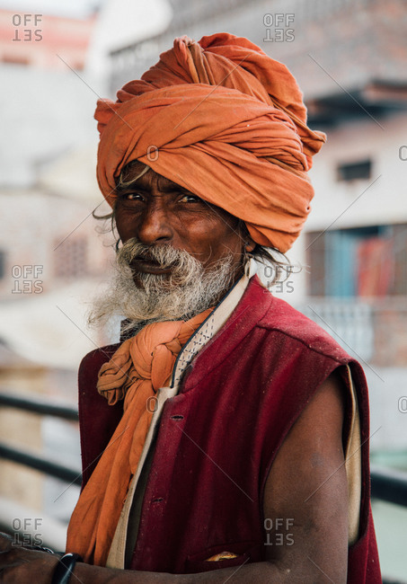 Varanasi, India - FEBRUARY, 2018: Aged bearded Hindu male in orange turban  wearing red sleeveless vest standing on street and looking at camera