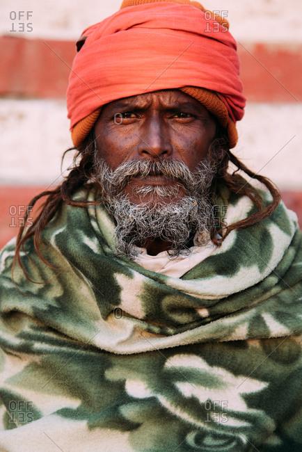 Varanasi, India - FEBRUARY, 2018: Close-up portrait of serious bearded Hindu male in turban looking at camera