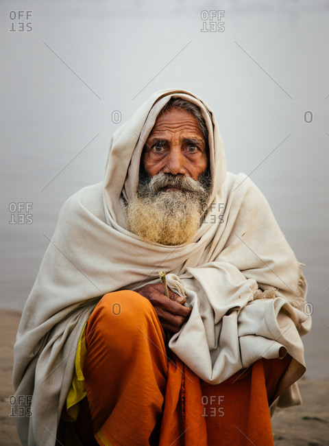 Varanasi, India - FEBRUARY, 2018: Elderly Indian man wearing traditional orange clothes sitting on river bank with fishing boats on water in early foggy morning