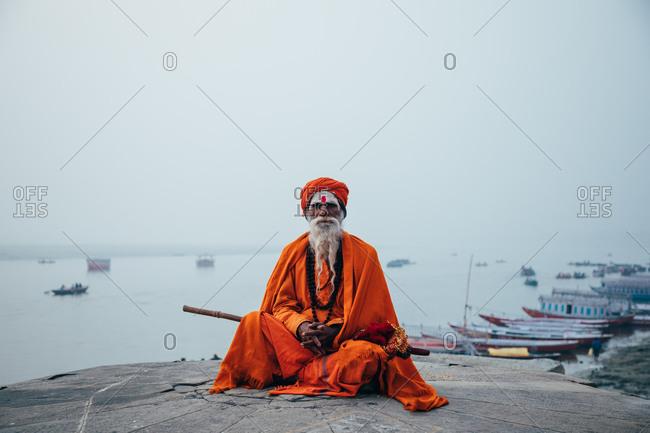 Varanasi, India - FEBRUARY, 2018: Aged bearded Hindu male in orange turban sitting on street and looking at camera
