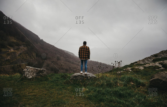 From below back view of unrecognizable male hiker in casual clothes standing on cliff in cloudy day in countryside