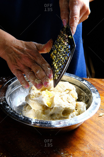 Unrecognizable female removing fresh lemon peel from metal grater over bowl with pastry dough in kitchen