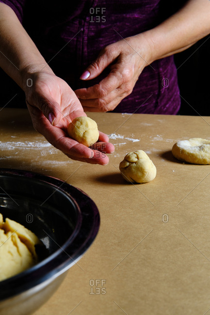 Unrecognizable lady rolling small balls from soft dough while cooking pastry on table in kitchen