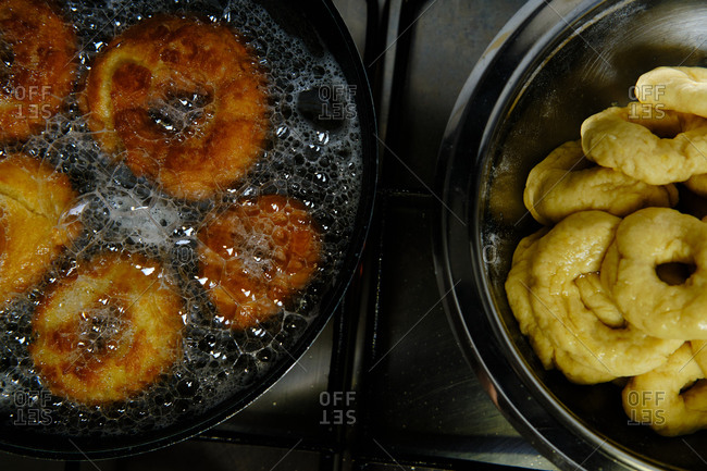 From above bunch of delicious doughnuts frying in hot bubbling oil on stove in kitchen