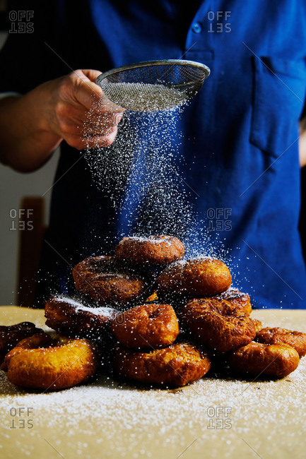 Unrecognizable person using sieve to spill powdered sugar on stack of fresh doughnuts while cooking pastry in kitchen