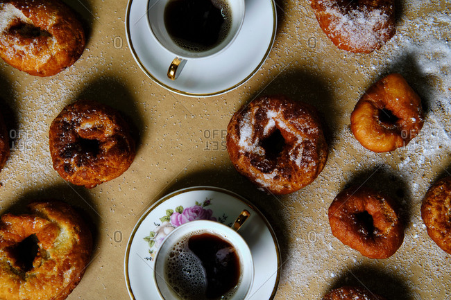 Top view of yummy doughnuts with powdered sugar and cups of hot tea placed on table at home