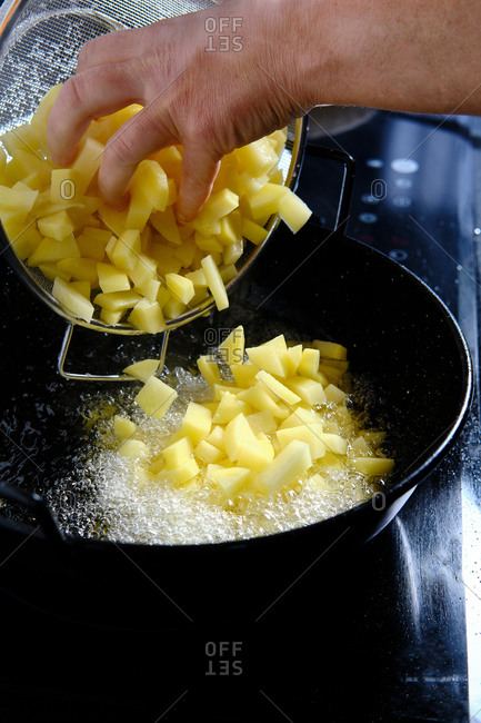 From above of crop chef pouring slices of potatoes from sieve to pan with boiling oil in modern kitchen