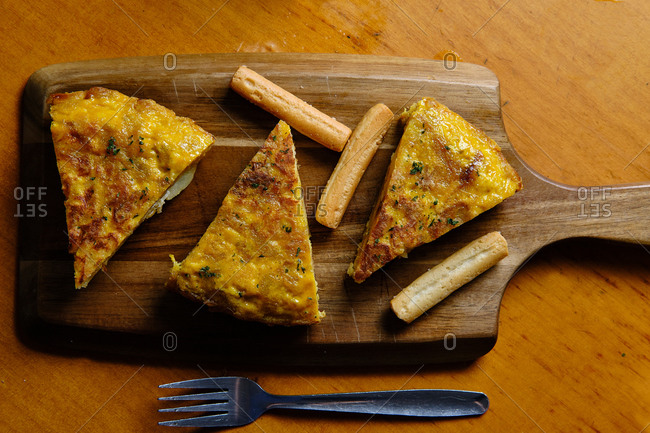 From above top view of slice of tasty Spanish omelet with potatoes and eggs on wooden table