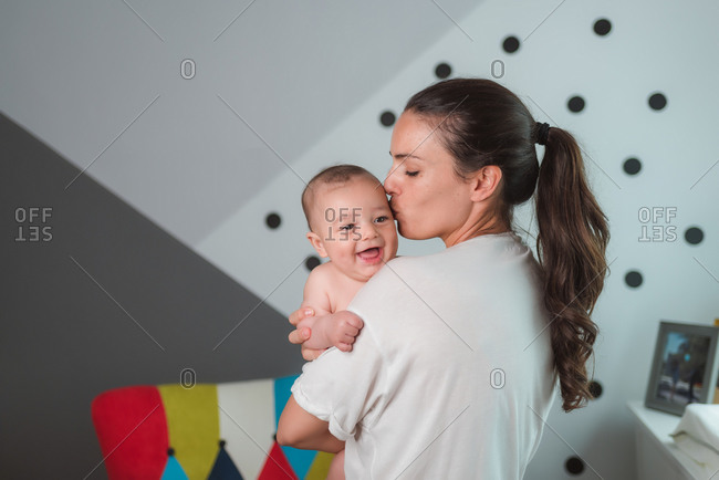Side view of satisfied young mother in casual wear laughing with content baby in arms during sunny morning