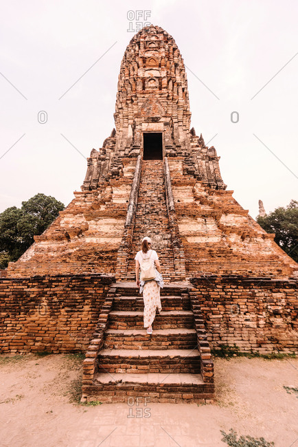 Back view of female traveler in casual clothes climbing on ancient stairs of big oriental old temple in Thailand