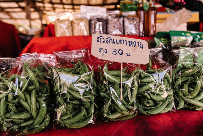 From above of green peas pods in packages on shelf with price tag in outdoors market in Thailand