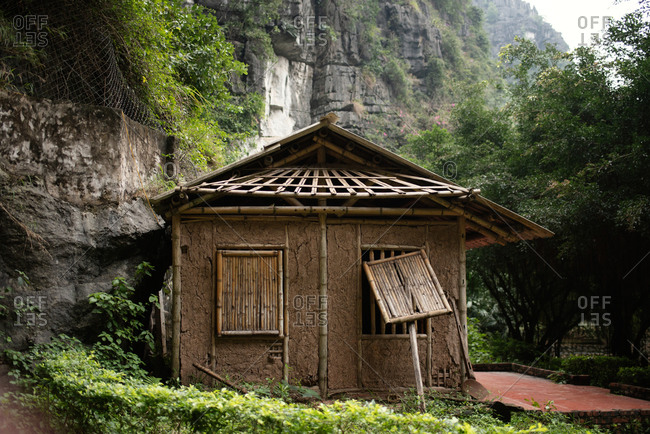 Aged abandoned small house among green plants and powerful rock in countryside
