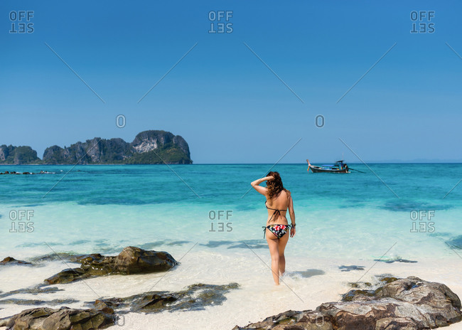 Back view of slim female tourist in swimsuit standing on sandy coast of turquoise ocean under blue sky in Thailand
