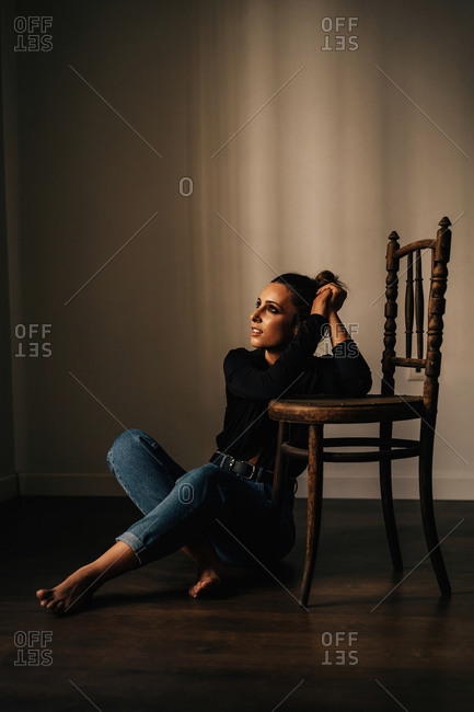 Young woman in black casual blouse and blue jeans sitting on floor while leaning elbows on chair and looking away