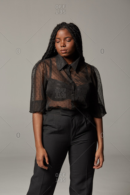 Attractive African American female in trendy transparent blouse and black trousers with closed eyes against gray background in studio