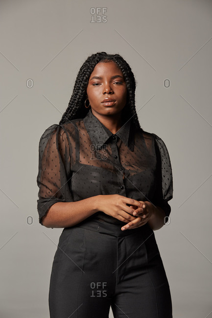 Attractive African American female in trendy transparent blouse and black trousers looking at camera against gray background in studio