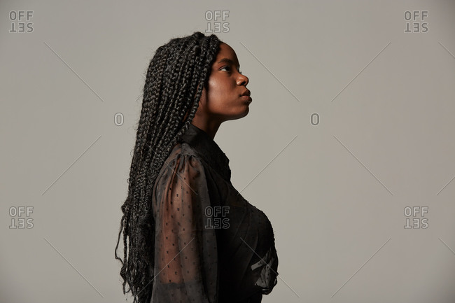 Side view attractive African American female with braids in trendy transparent blouse and black trousers with closed eyes against gray background in studio
