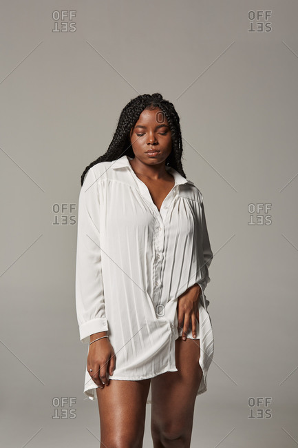 Sensual plus size African American lady with braids in trendy white dress standing with closed eyes against gray background