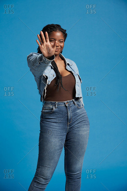 Positive beautiful African American woman with braids in denim outfit smiling with closed eyes against blue background