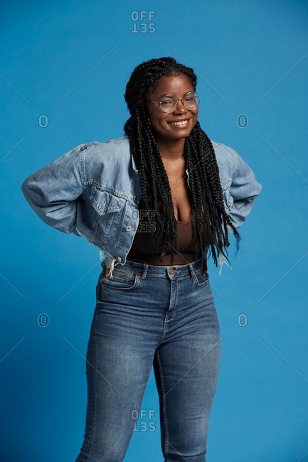 Plus size black female with braids in casual clothes smiling looking at camera against blue background