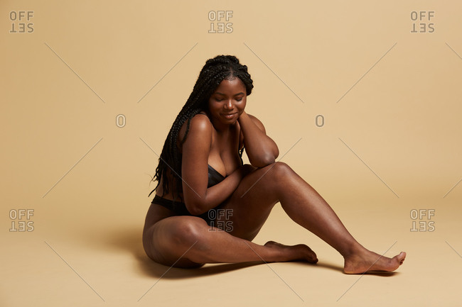 Curvy beautiful African American woman with braids in lingerie looking down sitting on the floor against yellow background