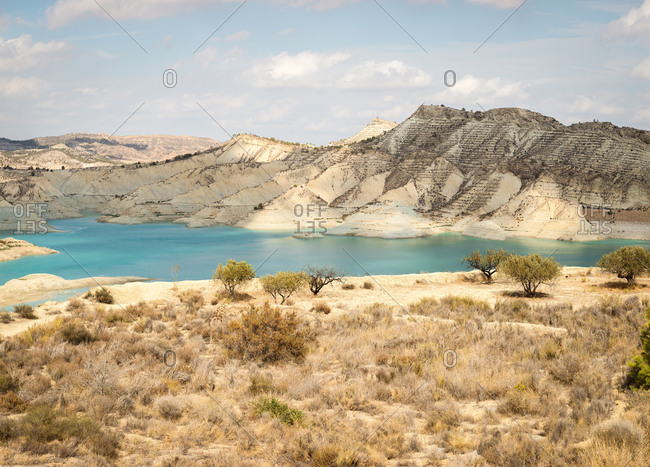 Clean water reservoir located between coast with dry grass and rough mountain on cloudy day in Algeciras, Spain