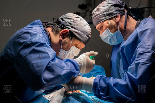 Surgeons and nurses in uniform concentrating and operating patient using special equipment in operating room of contemporary hospital