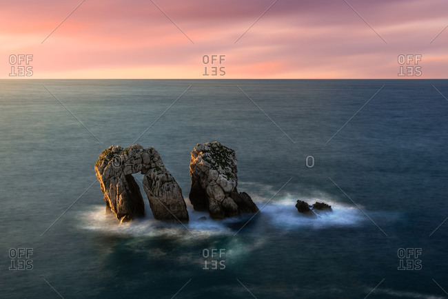 From above picturesque scenery of rough rocks among calm blue sea under colorful evening sky with sun beams breaking through clouds during twilight Costa Brava, Spain
