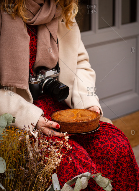 Unrecognizable woman in red dress with photography camera around neck sitting with delicious pie on lap