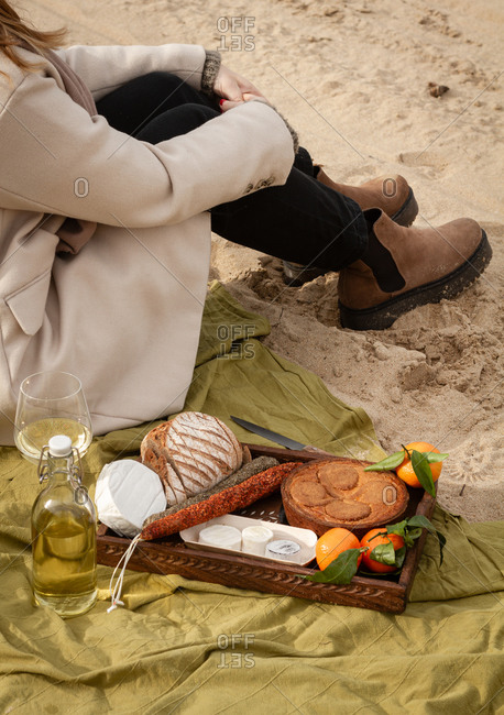 Unrecognizable female in elegant coat sitting on blanket near bottle and glass of white wine and tray with pie with tangerines and bread with cheese and sausages while resting on beach on weekend day