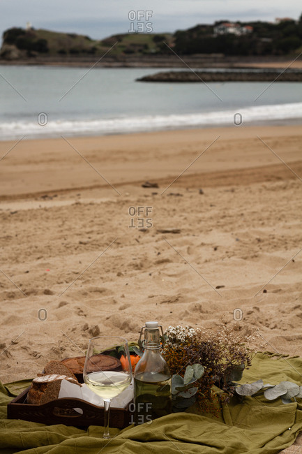 From above delicious pie with tangerines and fresh bread with cheese and sausages placed on tray near bottle, glass of wine and dry flowers on blanket during picnic on sandy beach with ocean on the background