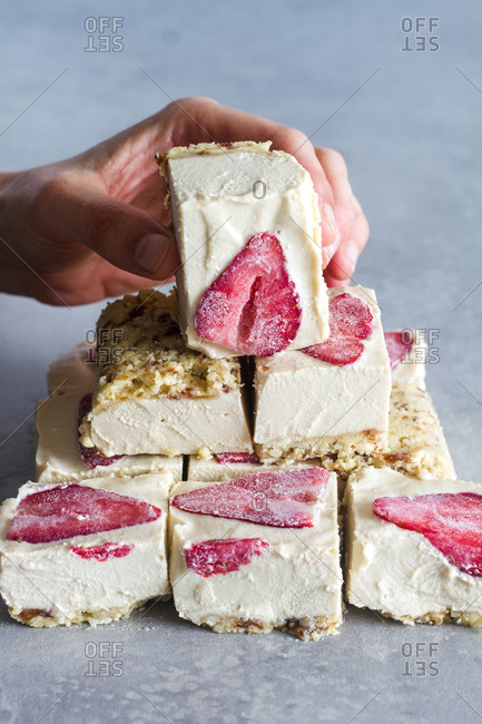Crop person holding piece of appetizing homemade cold dessert with white cream and fresh strawberry over marble table