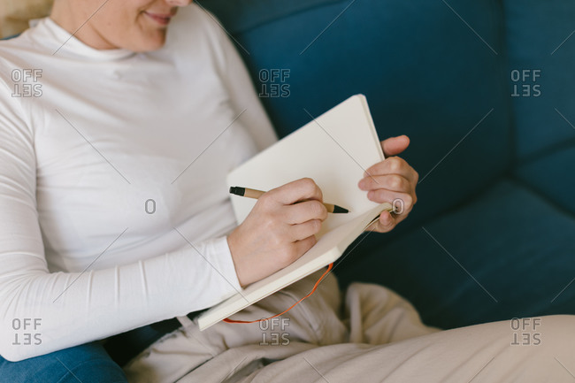 From above faceless lady in white shirt sitting on sofa and writing in notebook working on business project