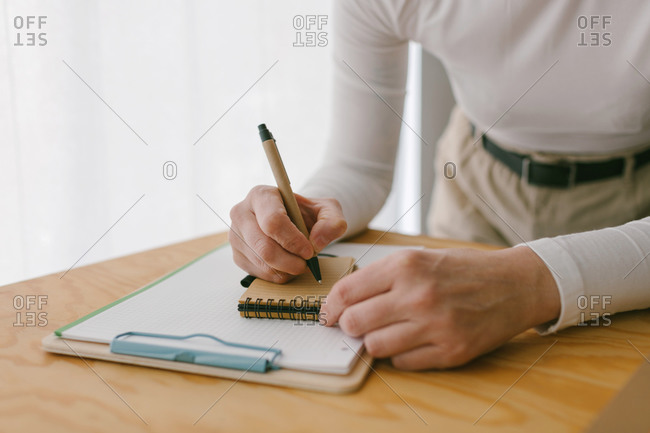 Faceless casual businesswoman bending on wooden table and writing in notepad with pen